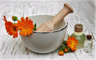 calendula flowers in mortar and massage oil on a wooden background